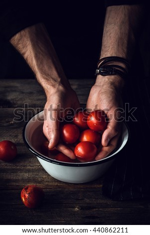Tomatoes in hands. Man washing freshly picked cherry tomatoes in bowl on rustic wooden table. Selective focus - stock photo