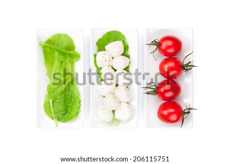 Tomatoes, mozzarella and green salad leaves. Isolated on white background - stock photo