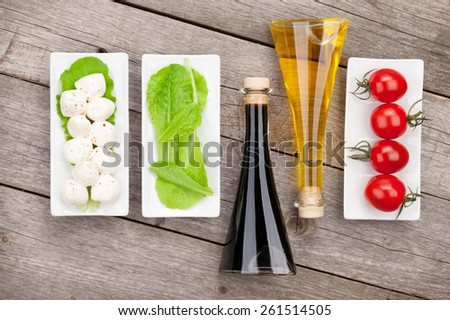 Tomatoes, mozzarella and green salad leaves with condiments on wooden table background - stock photo