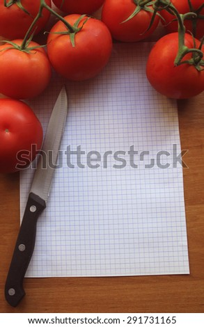 tomatoes on a wooden background with sheet of paper and knife - stock photo