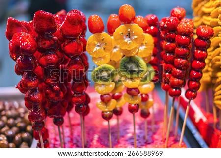 Tomatoes on sticks, traditional Chinese snacks. Located near Nanjing Confucius Temple scenic region, Nanjing City, Jiangsu Province, China. - stock photo
