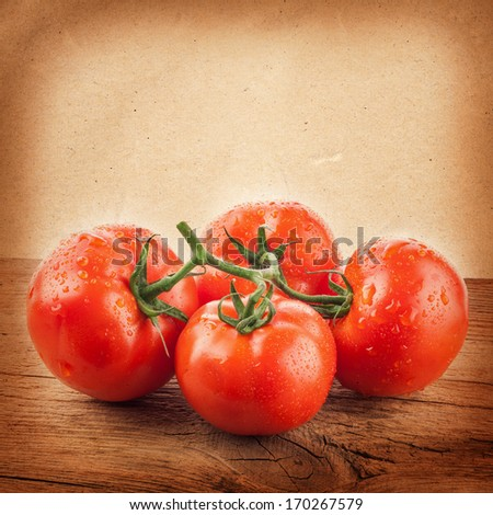 Tomatoes on the grunge yellow paper background - stock photo