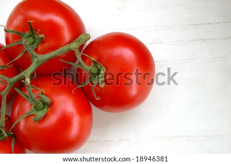 Tomatoes on the vine against rustic white background - stock photo