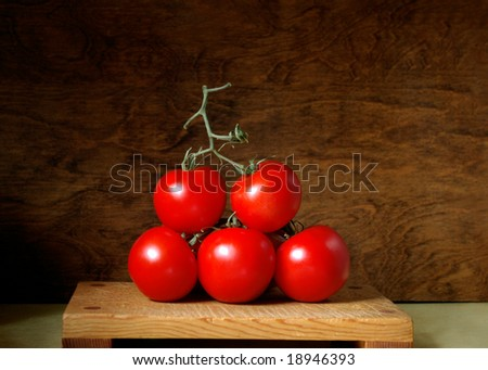 Tomatoes on the vine, stacked on cutting board - stock photo