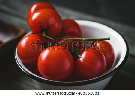 Tomatoes on vine in bowl. Rustic composition. Soft selective focus - stock photo