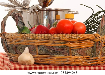Tomatoes, peppers and other veggies with oil and cook pot in the background. - stock photo