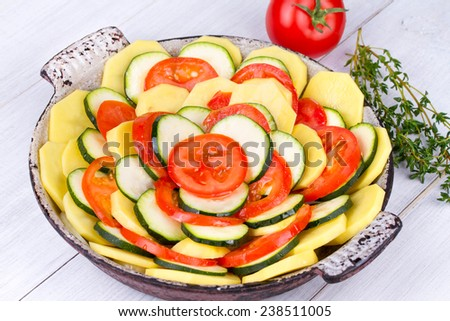 Tomatoes, potatoes and zucchini with thyme and parmesan cheese prepared for bake