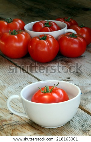 tomatoes red fresh organic in a white bowl on a wooden surface