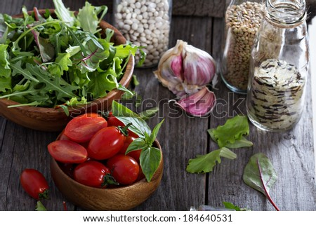 Tomatoes, salad leaves, beans and rice on a wooden table - stock photo