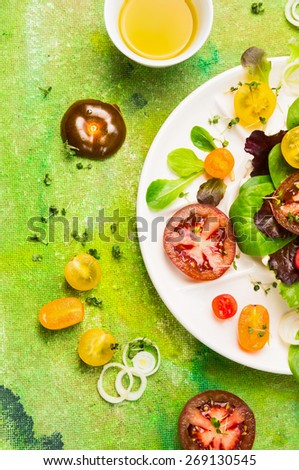 Tomatoes salad with olive oil on green background, top view, close up - stock photo