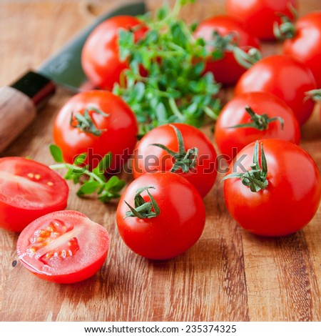 Tomatoes, thyme herb and knife on wooden cutting board. selective focus, shallow dof - stock photo