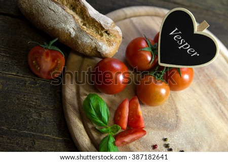 Tomatoes with basil and rustic bread on wooden table, heart with german word vesper which means meal