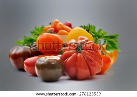 tomatoes with different forms and colors on dark background - stock photo