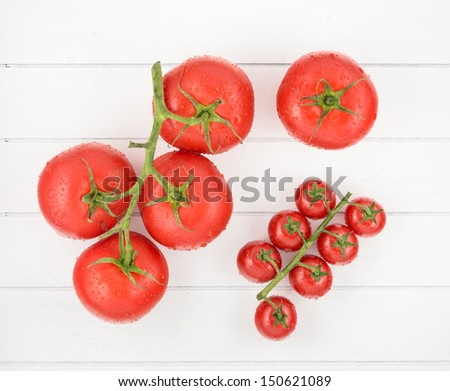 Tomatoes with drops on wood table - stock photo