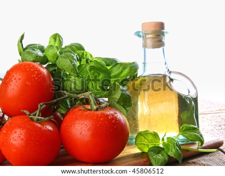 Tomatoes with fresh basil and bottle of olive oil