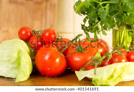 Tomatoes with vegetables sprinkled with water on a wooden table in the shallow depth of field - stock photo