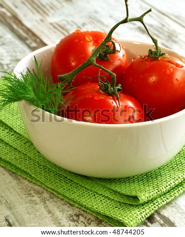 tomatoes with water drops in bowl on wooden - stock photo