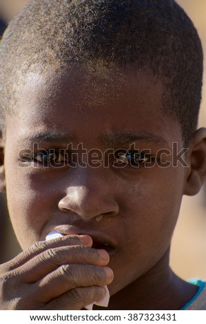 TOMBOUCTOU, MALI - JAN 05: Portrait of a young male boy looking at the camera with a sad expression on January 05, 2010 in Tombouctou, Mali.