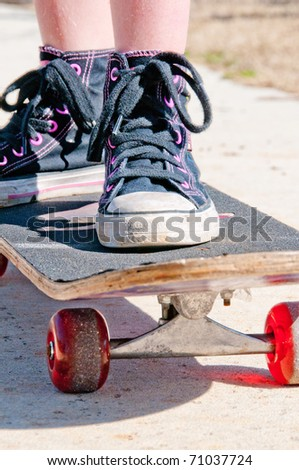 tomboy riding skateboard on sidewalk - stock photo