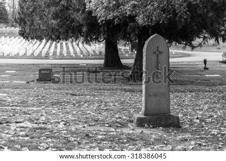 Tombstone and graves in graveyard landscape,black and white. - stock photo