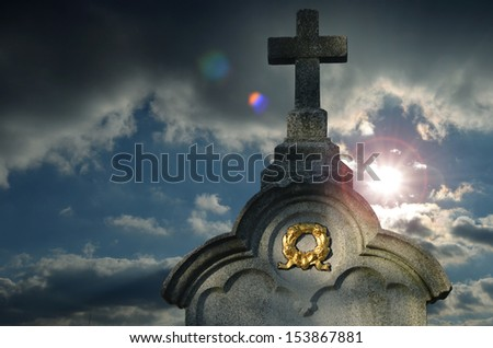 Tombstone cross with golden wreath and sunbeams - with lensflare - on stormy heaven - stock photo