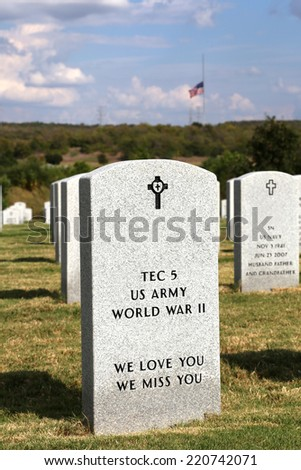 Tombstone in veterans memorial cemetary with flag flying at half-mast - stock photo