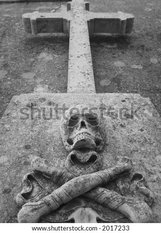 Tombstone with a cross, a scull and bones located in an abandoned cemetery.