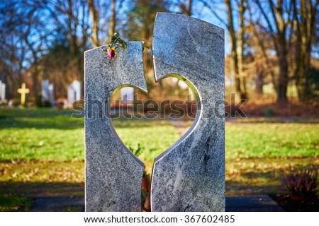 Tombstone with heart and rose / Gravestone with heart and withered rose on graveyard / Sorrow about loss of beloved ones - stock photo