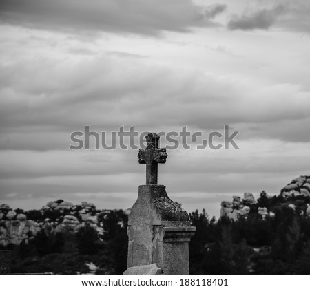 Tombstone with the cross at the old cemetery in Les Baux-de-Provence (Provence, France). Aged photo. Black and white. - stock photo