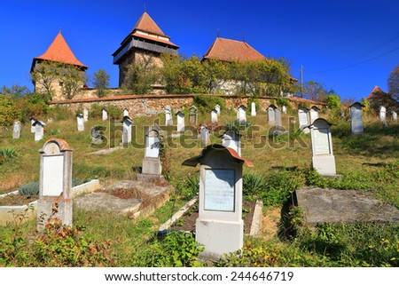 Tombstones from an old cemetery and fortified church from UNESCO world heritage list, Viscri village, Transylvania, Romania - stock photo