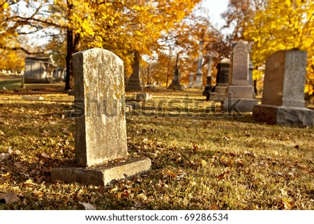 Tombstones in an old cemetery in the fall, selective focus - stock photo