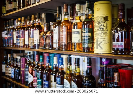 TOMINTOUL, UK - MAY 16: Various bottles of Scotch whisky on the shelf on May 16, 2015 in Tomintoul, UK. Scotch whisky must be made in a manner specified by law. - stock photo