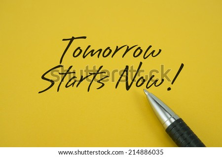 Tomorrow Starts Now! note with pen on yellow background - stock photo