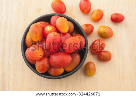 Tomoto fruit in a black bowl on wooden backgroud, Top view  - stock photo