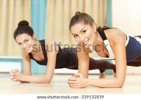Tone your body. Cropped shot of two cheerful girls doing planking exercise indoors - stock photo