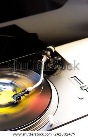 Tonearm on a spinning color vinyl. - stock photo