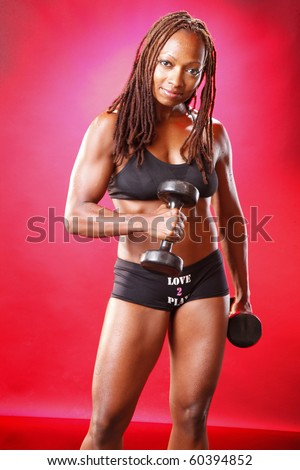 Toned african american and her dumbbell routine - stock photo