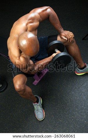 Toned and ripped lean muscle fitness man lifting weights on a curling bar. - stock photo