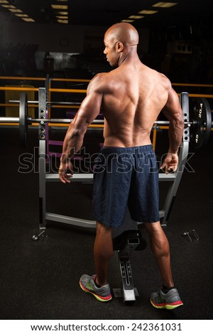 Toned and ripped lean muscle fitness man standing by a weight bench at the gym. - stock photo