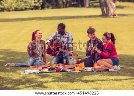 Toned. Best friends resting and relaxing picnic in park. People enjoying listening to guitar. Happy men and women drinking cocktails and singing songs. - stock photo