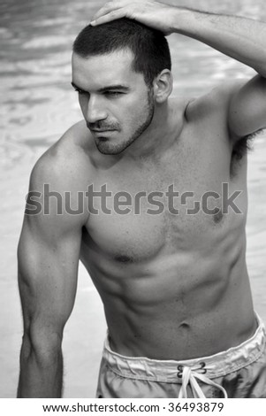 Toned black and white outdoor portrait of sexy young shirtless man in swim trunks against water background - stock photo