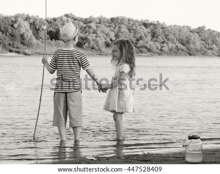 toned black and white shot of vintage style amusing boy and girl on the river summer day  - stock photo