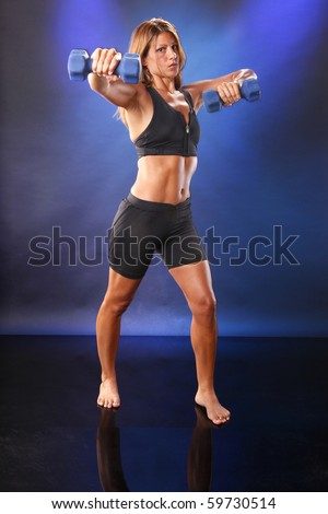 Toned blond working out with dumbbells - stock photo