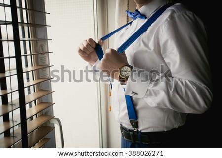 Toned closeup shot of businessman adjusting suspenders at office - stock photo