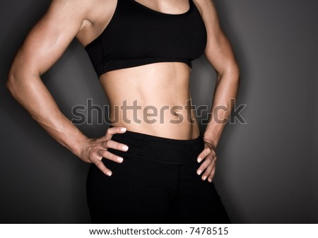 Toned female body builder - stock photo