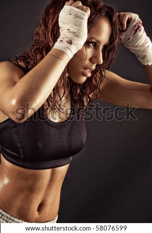 Toned female fitness boxer fighting with the shadow - stock photo