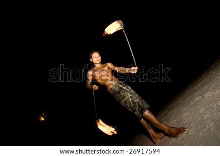 Toned fire dancer performing during the night on the beach