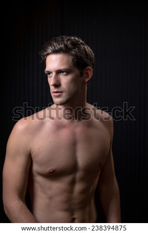 Toned fit shirtless young man with dark brown hair and blue eyes - stock photo