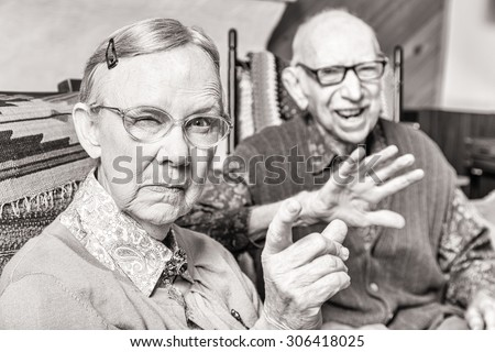 Toned image of angry old couple sitting in living room woman pointing - stock photo