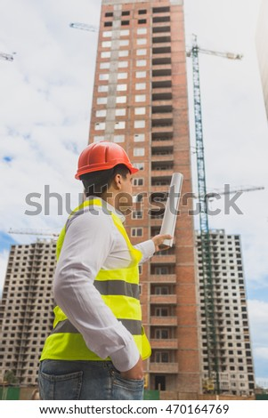 Toned image of architect in hardhat pointing at building under construction